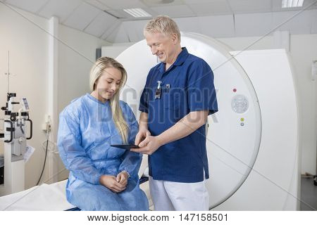 Male Doctor Showing Tablet Computer To Patient At MRI Machine