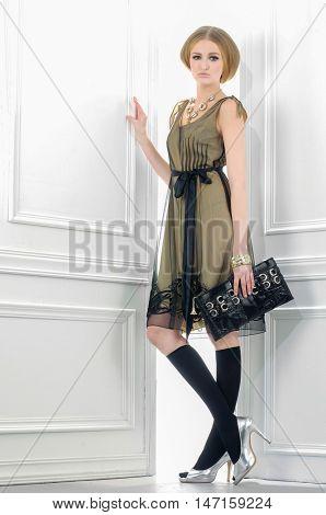 full-length fashion model holding little purse posing-light background