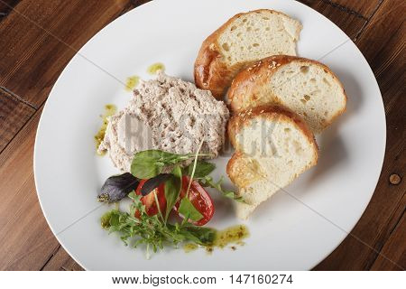 Rabbit pate with salad and bread in a white plate. White meat fillet. Wooden background.