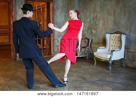 Beautiful girl in red dress and young man in hat dance tango in retro room