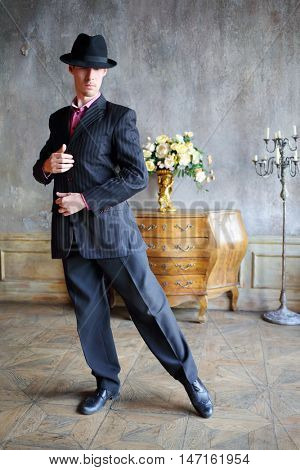 Young handsome man in black suit and hat dances tango in stylish retro room