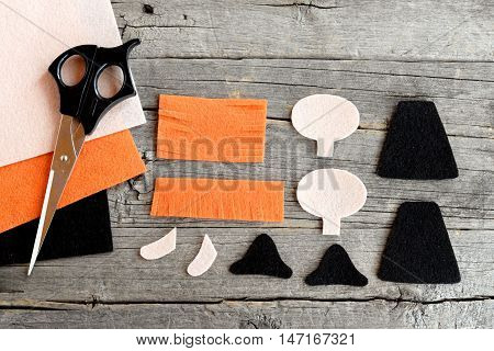 How to sew a Halloween witch doll. Step. Felt witch patterns, scissors, felt sheets on old wooden background. Halloween crafts project for children and beginners. Top view