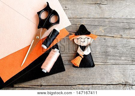 How to sew a Halloween witch decor. Step. Halloween felt witch with broom, beige and black thread, needle, scissors, felt set on old wooden background. Easy Halloween doll crafts for kids. Top view