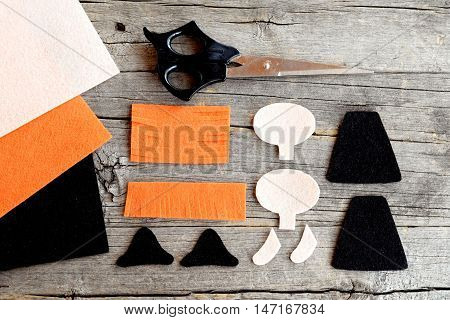 How to sew a Halloween witch doll. Step. Cut felt parts to create Halloween witch toy, scissors on old wooden background. Easy Halloween crafts project. Top view