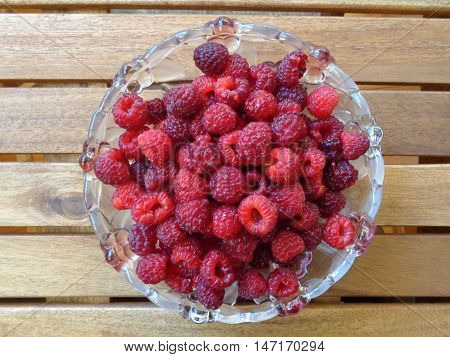 Fresh ripe raspberries on a glass plate, which stands on a wooden table. Suitable for design sites and magazines on cooking, agriculture,  ad creation