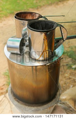 Pot of hot water boiler on wood fueled stove with coffee filter strainer bag. Traditional way to make Laos styled coffee called Kafe Lao and tea