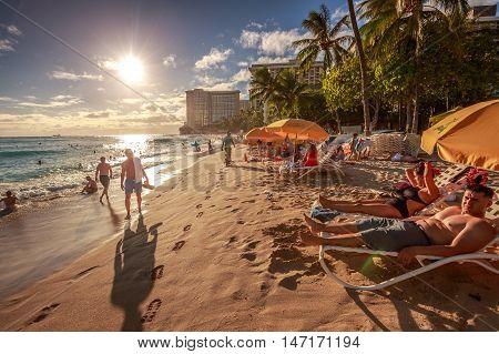 Waikiki, Oahu, Hawaii - August 18, 2016: tourist sunbathing and walking on the shore on Waikiki beach at sunset. Waikiki beach, South Shore, is neighborhood of Honolulu and the most popular of Hawaii.