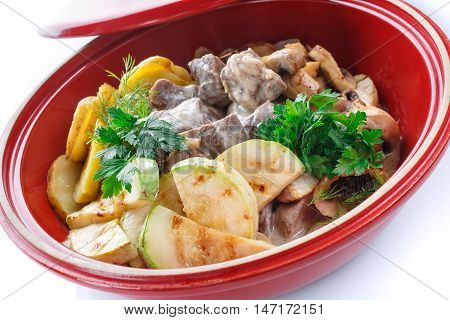 vegetable stew with meat, mushroom and herbs stewed in a pot on a white background