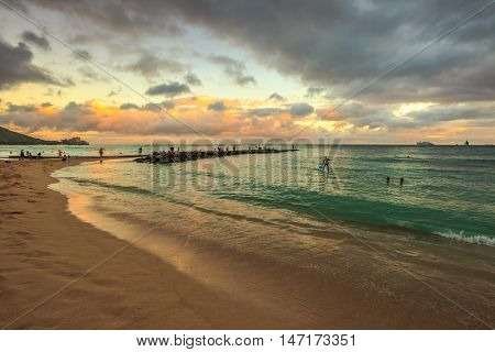 Waikiki, Oahu, Hawaii - August 20, 2016: twilight at Waikiki beach. Waikiki beach is a beautiful place to enjoy the sunset over the ocean. People practice surfing paddling and swimming.