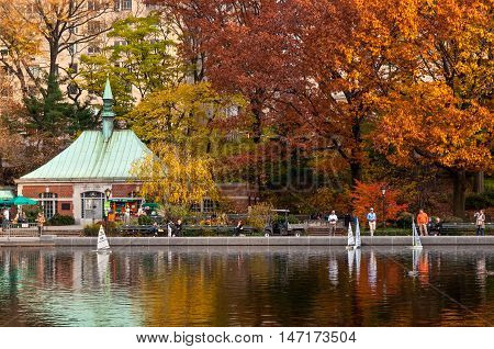 New York City USA - November 14 2011: A people sailing a model boats at the Conservatory Water in New York's Central Park at November 14 2011. Central Park's pond is popular with tourists who rent radio-controlled sailboats one lever on the controls turni