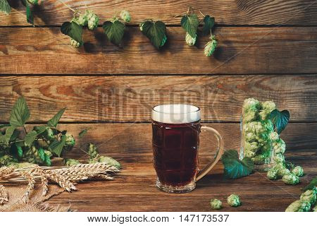 Beer glass with lager dark lager brown ale malt and stout beer on table in bar or pub still life with wooden background vintage filter