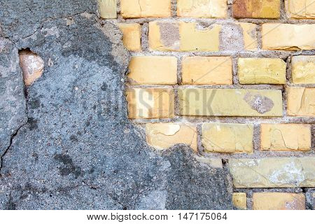 Cracked concrete on vintage brick wall background
