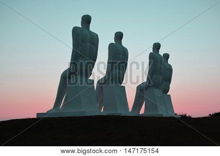 Fire mænd kigger ud over havet, på en solnedgang