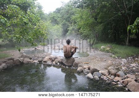 Man in meditation at the Tha Pai Hot springs in Pai, Thailand