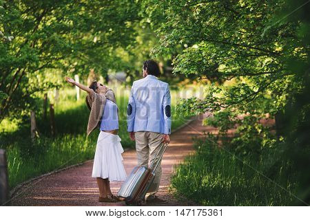 Couple on the road in park. The girl is brought up. The man costs a back with a suitcase