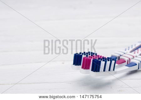 Three toothbrushes on white wooden background elevated view with copy space.