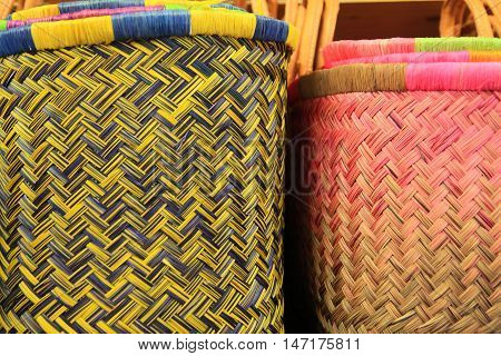 Colorful wicker reed baskets in blue yellow and pink with herringbone pattern