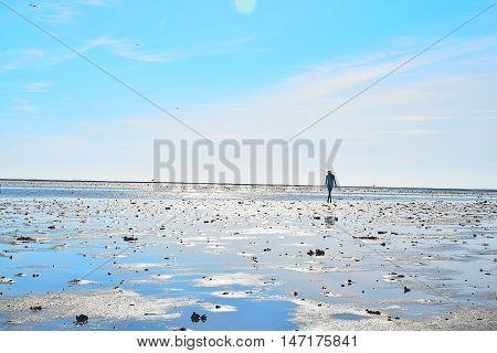 Kvinde går ud mod vandet som er tilbagetrukket på en sommerdag