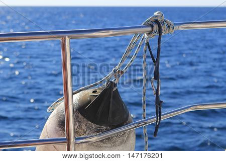 Fender Ball Or Anchor Ball Hanging From The Shiny Chrome Handrail Of A Boat With Blue Sea In Backgro