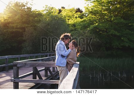 Loving couple look at each other standing on the bridge