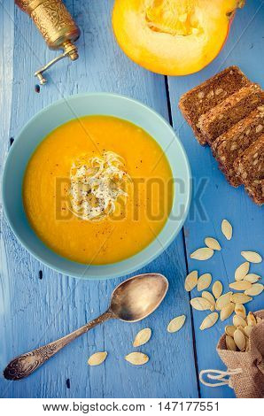 Pumpkin soup with cream cheese and pumpkin seeds on blue wooden background. Pumpkin soup with fresh pumpkins. Halloween Thanksgiving Autumn food concept. Top view.