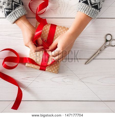 Woman's hands wrapping christmas or other holiday handmade present in paper with red ribbon. Making bow at present box, decoration of gift. Scissors on white wooden table, top view.