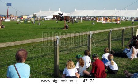 Kids And Woman Watching A Showjumping Event/Sport.