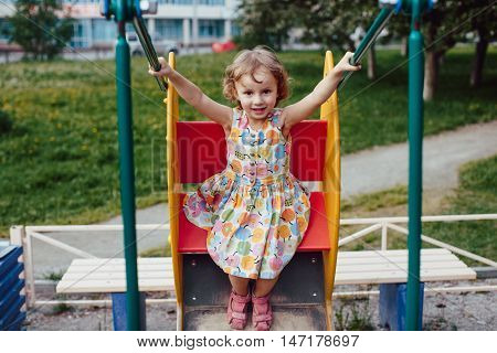 Baby girl swinging on a swing at the playground in the city park