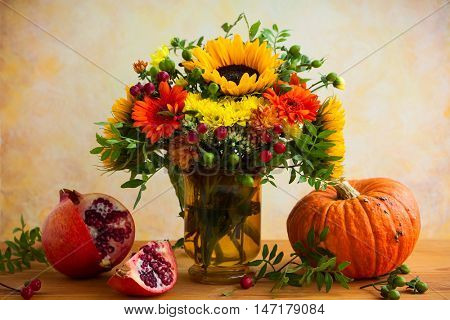 Autumn still life with flowers, pumpkin and fruits