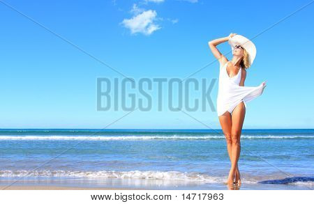 Young woman standing on a beach and enjoying the sun