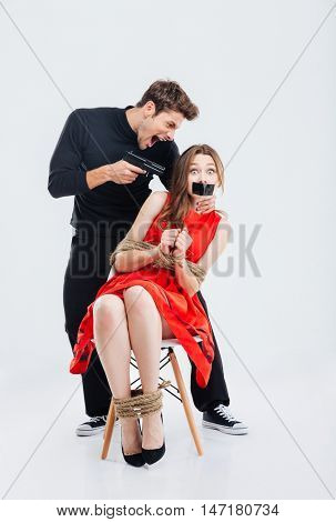 Cruel criminal man threatening scared woman by gun isolated on the white background
