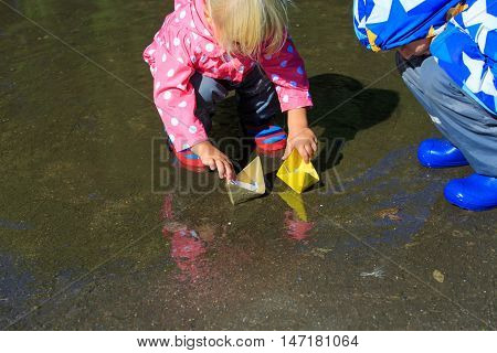 little boy and girl playing with paper boats in water puddle
