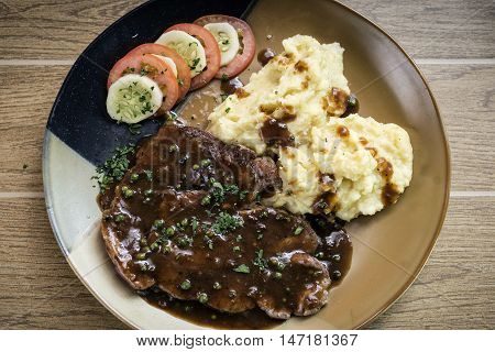 beef steak meal with mashed potato and gravy sauce on table