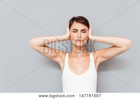 Young woman with eyes closed covering her ears with palms isolated on a gray background