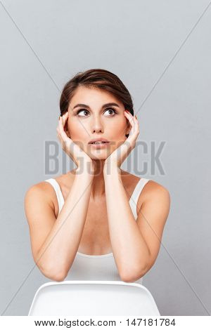 Thoughtful brunette woman sitting on the chair and looking away isolated on a gray background
