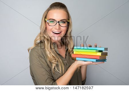 Portrait of a happy excited student girl wearing glasses over gray background, taking books for new educational season, enjoying education in the university