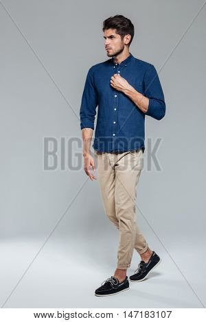 Full length portrait of a casual young man fastening button isolated on a gray background
