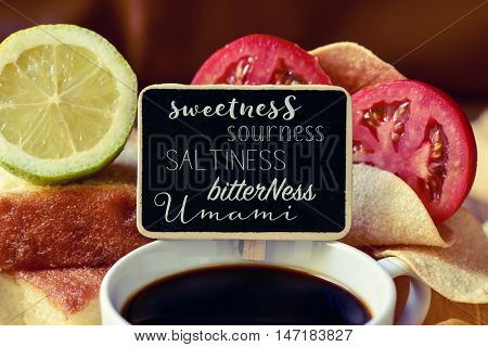 closeup of a black chalkboard with the name of different tastes, such as sweetness, sourness, saltiness, bitterness or umami, placed on a pile of some different products representative of this tastes