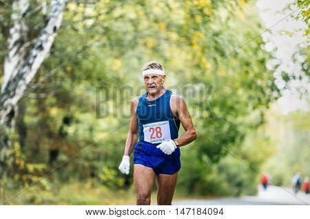 Chelyabinsk Russia - September 11 2016: oldest male runner running in autumn Park during City marathon