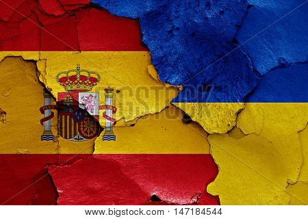 flags of Spain and Ukraine painted on cracked wall