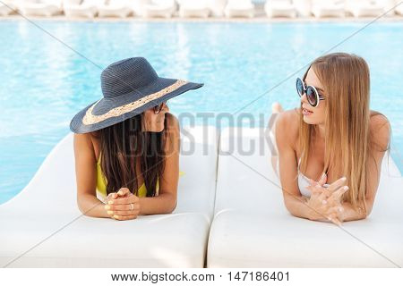 Two pretty young women lying on deckchair outdoors at the swimming pool and talking