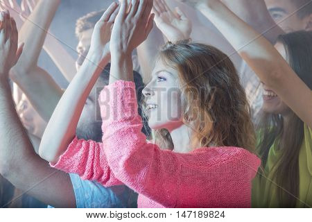 Shot of a group of young people clapping their hands at a party