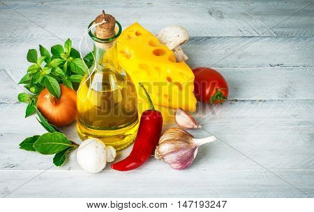 Ingredient for italian food with herbs and tomato on old wooden board words copyspace