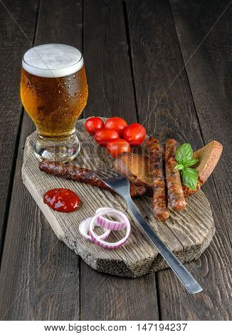 Sausages with cherry tomatoes beer bread and onion on wood table