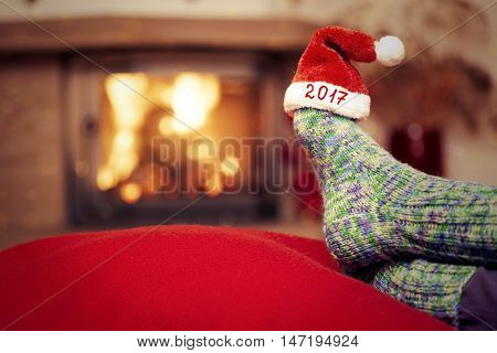 Feet in woollen socks by the fireplace. Woman relaxes by warm fire and warming up her feet in woollen socks. Christmas female legs in socks on the background of a burning fireplace.