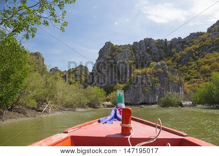 long tail fishing boat floating in a sea with limestone mountains and rock cliff mountains
