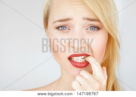 Beautiful red woman with confused look portrait. Young carroty girl with freckles feels at a loss. Thinking female pondering over something and biting her finger.