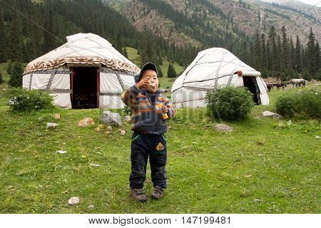 BARSKOON, KYRGYZSTAN - AUG 3, 2013: Boy plays with soap bubbles near farmer house in a valley at mountains of Central Asia on August 3, 2013.