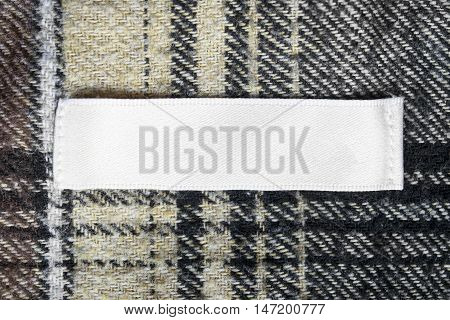 Blank white clothes label on wool cloth as a background