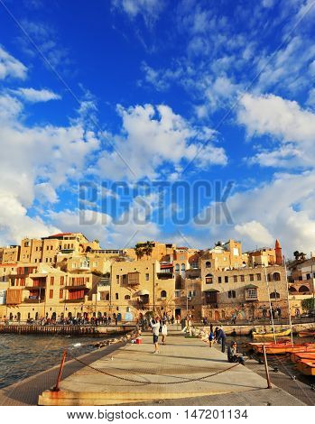 TEL AVIV, ISRAEL - NOVEMBER 22, 2014: Sunny day. The ancient port of Old Jaffa, Tel - Aviv. People walk on the promenade on warm autumn day